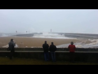 Five people were injured after a massive rogue wave flooded a beach in Portugal.