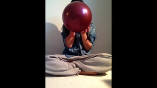 Asian girl blow up a wine red balloon until it pops